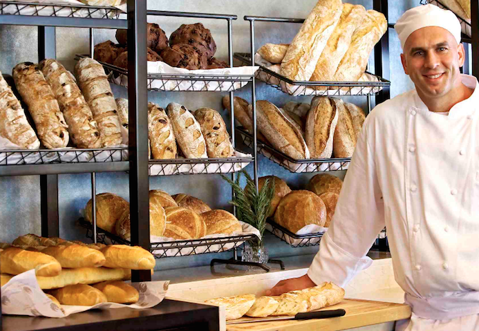 A baker standing in front of his produce within a bakery. Sugar is one of the most important ingredients used in bakery foods. Keeping an eye on the global market will be more important than ever.