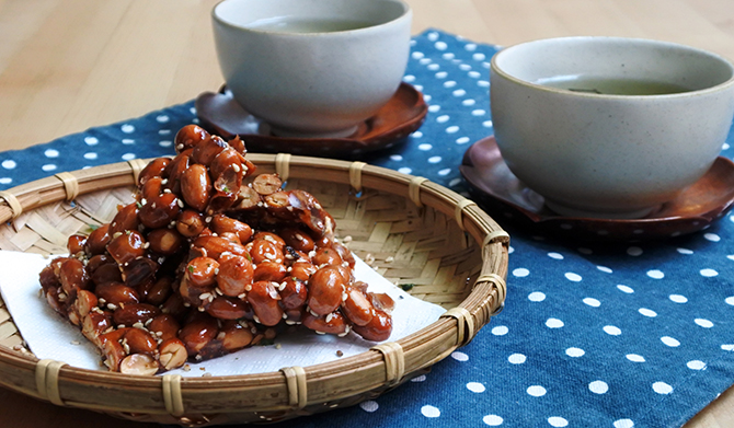 Traditional Chinese tea treats: peanut and sesame brittle (Chinese peanut candy or Fah Sung Thong). Served with green tea