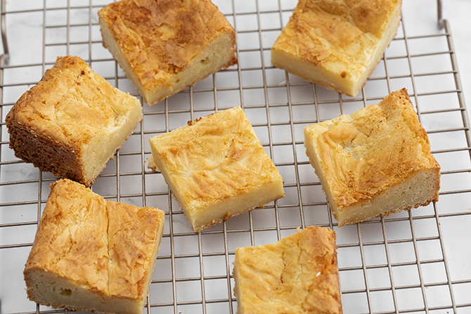 Pieces of freshly baked white chocolate brownie blondie squares on cooling tray.