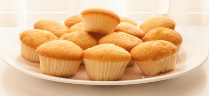 stack of homemade golden syrup cupcakes on white plate.