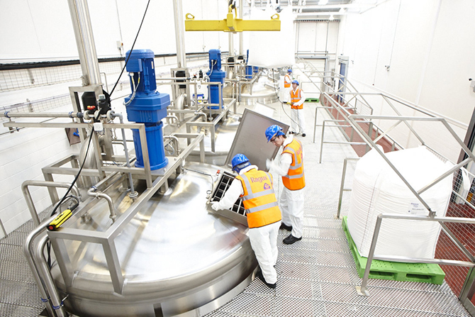 Workers in high visibility health and safety clothing and helmet looking into bulk sugar syrup vat in production facility.