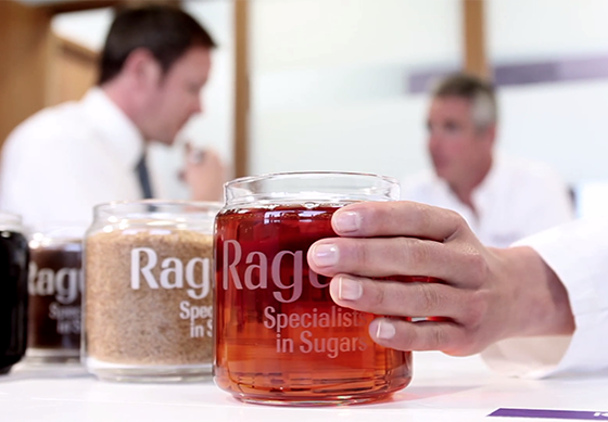 Ragus jar of crystalline and sugar and syrup being picked up by hand in lab coat opposite suits