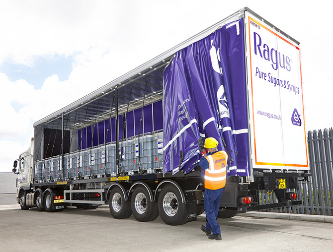 Ragus lorry being loaded by worker in high visibility clothing and a safety hard hat