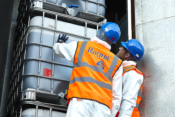Two people in safety hats and high visibility jackets checking intermediate bulk containers of sugar syrup.