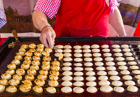 """Freshly baked traditional Dutch mini pancakes called """"poffertjes"""" on the metal oven tray."""