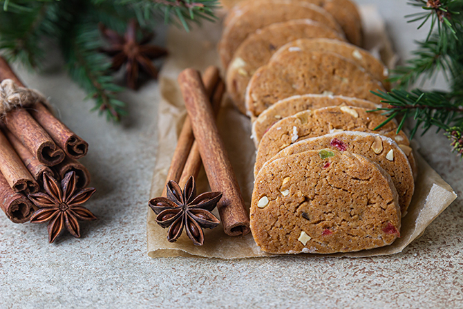 Danish spicy butter cookies with candied fruits, cinnamon sticks and anise, light background. Festive Christmas or New Year background with fir branches.