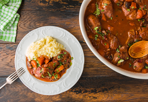 Coq au Vin, traditional French recipe of chicken braised in red wine with carrot and mushrooms.