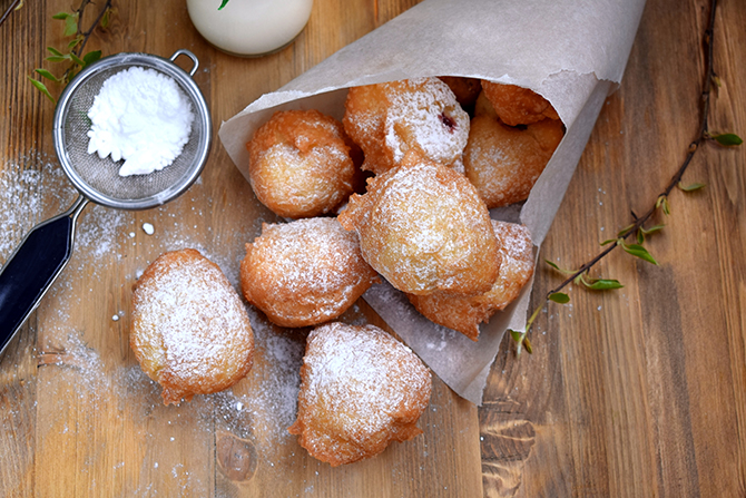 French Beignet covered with sugar powder on a wooden table.