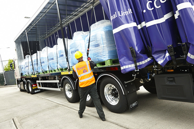 Staff member in high vis and hard hat securing intermediate bulk containers (IBCs) in an HGV.