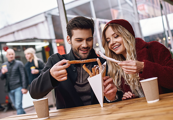 Close-up of young couple eating Spanish churros at the street food market.