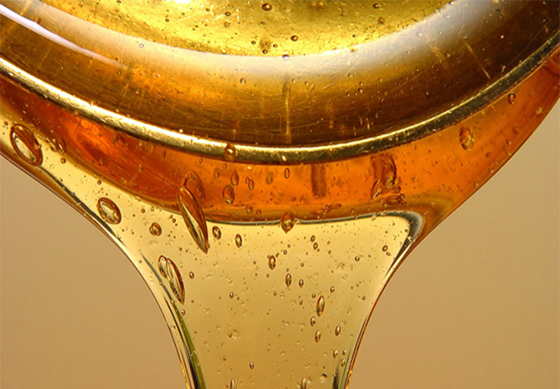 Close-up image of golden syrup pouring into container
